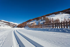 Snowcapped road to alpine resort with ski tracks Royalty Free Stock Images