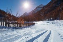 Snowcapped road to ski resort with snowcat tracks Royalty Free Stock Photo