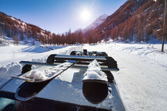 Snowcapped skis fastened on car roof rails Stock Images