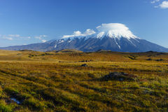 Snowcapped Tolbachik volcano covered by lenticular cloud Stock Photos