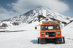 Snowcat auf schneebedeckten Steigungen des Berges auf Hintergrundvulkan Stockfoto