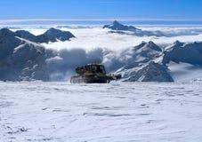 Snowcat avec des gens allant vers le haut la côte Photographie stock