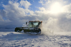 Snowcat evening working on a slope Royalty Free Stock Images