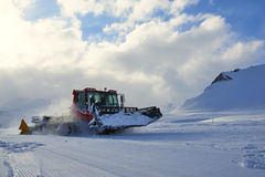 Snowcat evening working on a slope Royalty Free Stock Photo