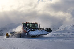 Snowcat evening working on a slope Stock Images