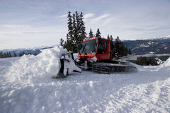Snowcat grooming. A snowcat grooming machine works the snow at a ski area into perfect piste skiing conditions Stock Photos