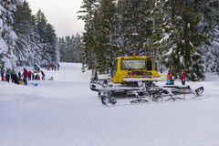 Snowcat preparing slope for children with parents sledding Royalty Free Stock Images