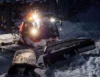 Snowcat preparing a slope in mountains Stock Photography
