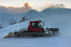 Snowcat rides to work in the evening Stock Images
