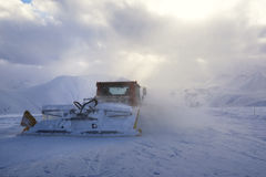 Snowcat rides to work in the evening Stock Photography