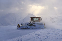 Snowcat rides to work in the evening Stock Photos
