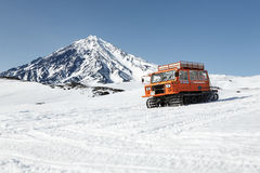 Snowcat transportation of people on snowy slopes of volcano Stock Photo