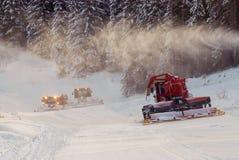 Snowcats at mountains. Snow tracks made by ratraks Stock Photo