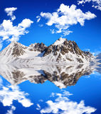 Snowcovered high mountain besides a lake with nice Royalty Free Stock Photos