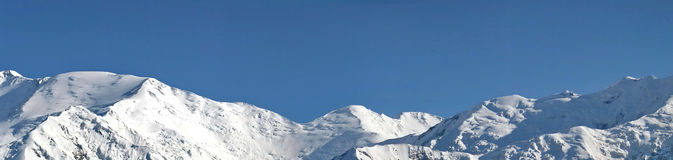 Snowcovered high mountain. With blue sky Royalty Free Stock Photography