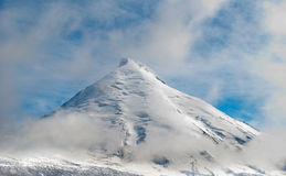 Snowcovered high mountain in clouds Stock Images