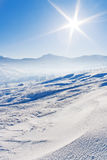 Snowcovered mountains under blue sky. And shiny sun Royalty Free Stock Images