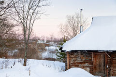 Snowcovered wooden house in country Stock Images