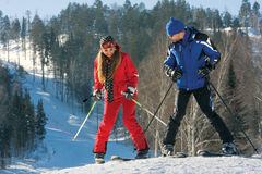 Snowdrift. A beautiful young woman on ski along with a handsome instructor against a snowfield Stock Image