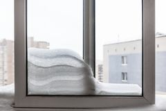 Snowdrift between frames on balcony in winter. Snowdrift between frames on balcony of residential house in Moscow city in winter royalty free stock images