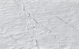 Snowdrift on ice with clefts Stock Photography