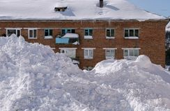 The snowdrift lies in front of the brick house. Severe climate in the village of Belogorsk, Tisulsky district, Kemerovo region. Siberia. Russia Royalty Free Stock Photography