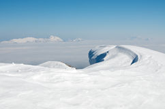 Snowdrift in the mountains. Wave shaped snowdrift. Mountains in the background. Blue sky. Julian Alps, Slovenia. Karavanke mountain range in the background Stock Photography
