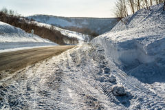 Snowdrifts and rural road Stock Photos