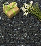 Snowdrop花和礼物盒在鲜绿色珍珠花岗岩worktop 免版税图库摄影