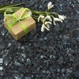 Snowdrop花和礼物盒在鲜绿色珍珠花岗岩worktop 库存照片
