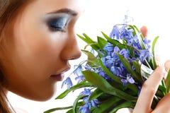 美丽的青少年的女孩气味和享受snowdrop花芬芳  免版税图库摄影