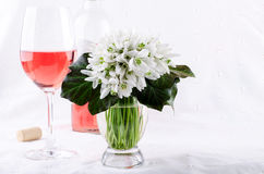 Snowdrop bouquet, white spring flowers and pink wine on light background. Copy space Royalty Free Stock Photos