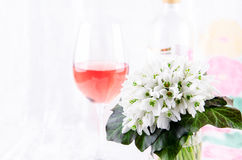 Snowdrop bouquet, white spring flowers and pink wine on light background. Copy space Stock Photography