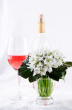 Snowdrop bouquet, white spring flowers and pink wine on light background. Copy space Royalty Free Stock Image
