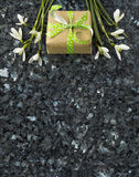 Snowdrop flowers and gift box on emerald pearl granite worktop Stock Photo