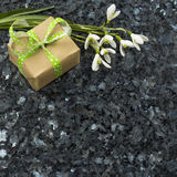 Snowdrop flowers and gift box on emerald pearl granite worktop Stock Photos