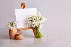 snowdrops花束和有一个白皮书和微型瓶子的一个小画架在灰色背景 免版税图库摄影