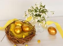 Snowdrops de oro de los huevos de Pascua Fotografía de archivo