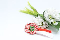 Snowdrops and red and white string martisor on white with copy space east european first of march tradition celebration. Snowdrops and red and white string Royalty Free Stock Photos