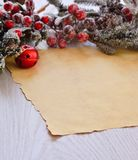 Snowed fur-tree branch with berries above wrapping paper Stock Photo