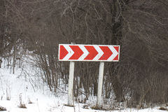 Snowed guide road sign of turn and tree Royalty Free Stock Photo