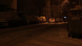Snowed Neighborhood. Street with parked cars view, during the night, in the pale light of public street lanterns stock video footage