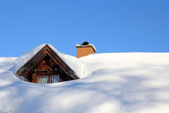 Snowed roof window of an old wooden house Royalty Free Stock Images