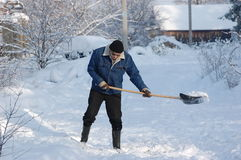 After snowfall. Adult man clean owns road to home  against snow.Near Kiev,Ukrainern Stock Photo