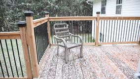 Snowfall on the back deck. First snowfall coming down onto a chair on the patio or porch stock footage