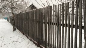 Snowfall on the background of an old wooden fence. The Snowfall on the background of an old wooden fence stock video footage