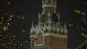 Snowfall on the background of the Spassky tower. New Year`s fair tents near the tower stock footage