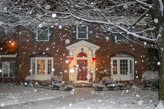 Snowfall on beautiful brick house with columns and bay windows with Christmas tree light up and red sled and wreath on porch royalty free stock images