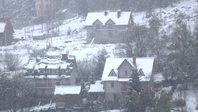 Snowfall calmly and quietly falls on village of wooded hill stock video