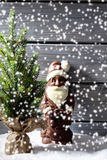 Snowfall with christmas tree and chocolate santa clause on heap of snow against wooden background Stock Images